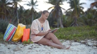 Woman after shopping using tablet PC on the beach — Stockvideo