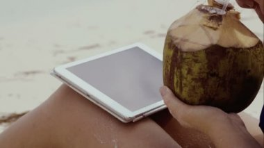 Woman using touch pad and having coconut drink — Vídeo Stock