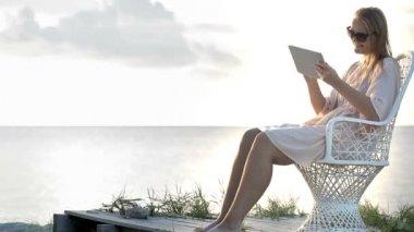 Woman near the sea watching photos using pad — Stock Video