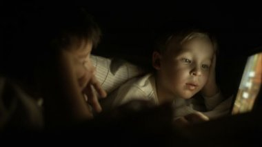Two boys lying in bed at night and using pad — Vídeo stock