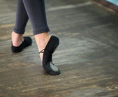 Close up view to ballerinas legs in pointes on wooden floor — Stockfoto