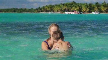 Mother and son playing in clear sea water — Stock Video
