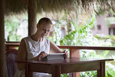 Smiling woman using tablet computer in cafe during vacation — Stock Photo
