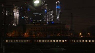 Passenger train passing through the city at night — Video Stock