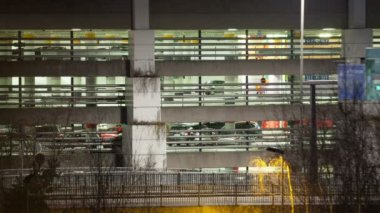 Timelapse of traffic near parking deck at night — Stock Video