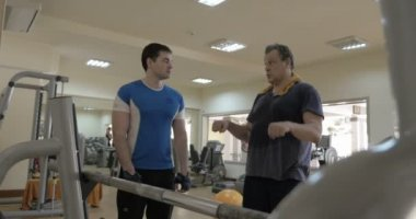 Gym instructor giving consultation to a man — Stock video