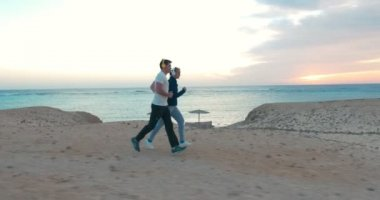 Young people jogging on the beach at sunset — Stockvideo