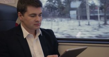 Young businessman working with pad in the train — Stock Video