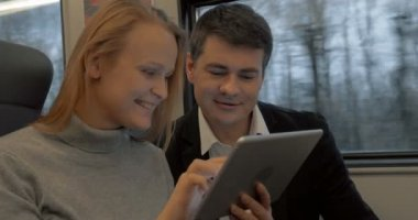 Young people working with pad and talking in the train — Vídeo stock