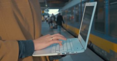 Woman using laptop by train at the station — Stock Video