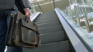Businessman with leather briefcase riding on escalator — Stock Video