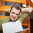 Man entertaining with laptop and music at home — Stock Photo #78258288