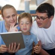 Parents and son with tablet PC at the airport — Stock Photo #78258490