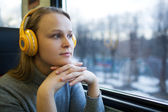 Woman traveling by train with favorite music — Stock Photo