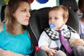 Mom looking at her son in child safety seat — Stock Photo