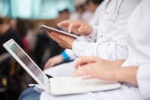 Medical students with pad and laptops in auditorium — Stock Photo