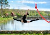 Rhythmic gymnast girl exercising with ribbon outdoor — Stockfoto