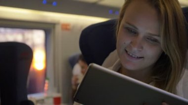 Smiling woman with touch pad in express train — Stockvideo