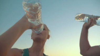 Two People Drinking Water from Plastic Bottles — Stock Video