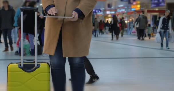 Mujer utilizando la Pc de la tableta mientras se espera para la salida — Vídeo de stock