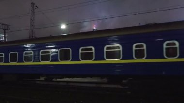 Passenger train arriving to station in the evening — Stock Video
