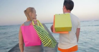 Friendly young couple walking on the pier after shopping — Stock Video