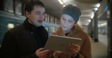 Young people discussing something using pad at metro station — Stock Video