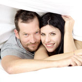 Couple in love smiling under bed sheet — Stock Photo