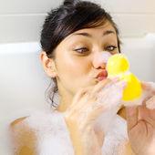 Woman having fun with yellow duck in bathtub — Stockfoto