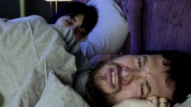 Man crying in bed with sleeping girlfriend — Stock Video