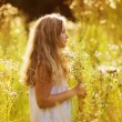 Cute little girl among white wildflowers — Stock Photo #57163965