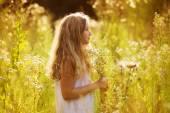 Cute little girl among white wildflowers — Stock Photo