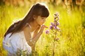 Girl touches to a wild flower — Stock Photo