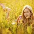 Happy girl lying among the wildflowers — Stock Photo #59646845