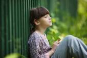 Happy little girl sitting and dreaming — Stock Photo