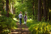Boy with girl walking in the summer forest — Stock Photo
