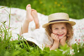 Happy girl in a hat lies and laughs — Stock Photo