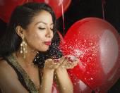 Beautiful young woman in black dress blowing confetti — Stock Photo