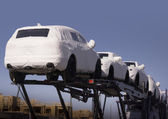 New auto cars under wraps being delivered on truck — Foto de Stock