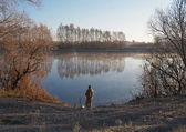 A fisherman fishes on the riverside  by a cold autumn morning — Stock Photo