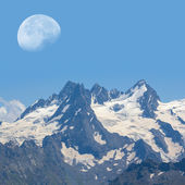 Huge moon above a snowbound rock — Stockfoto
