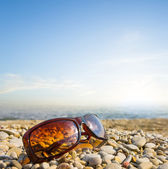 Sun glasses on a sea coast — Stock Photo