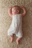 Baby sleeping  on a carpet — Stock Photo