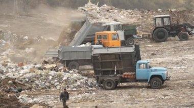 Garbage trucks unload garbage on a dump — Stock Video