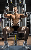 Bodybuilder on gym apparatus — Stock Photo