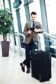 Zakenman met behulp van tablet pc op luchthaven — Stockfoto