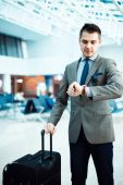 Businessman checking time at airport — Stock Photo