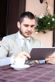 Businessman using digital tablet in cafe — Stock Photo