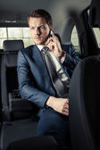 Businessman in the car with mobile phone — Stockfoto