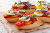 Crostini with anchovies, tomatoes and egg — Stock Photo